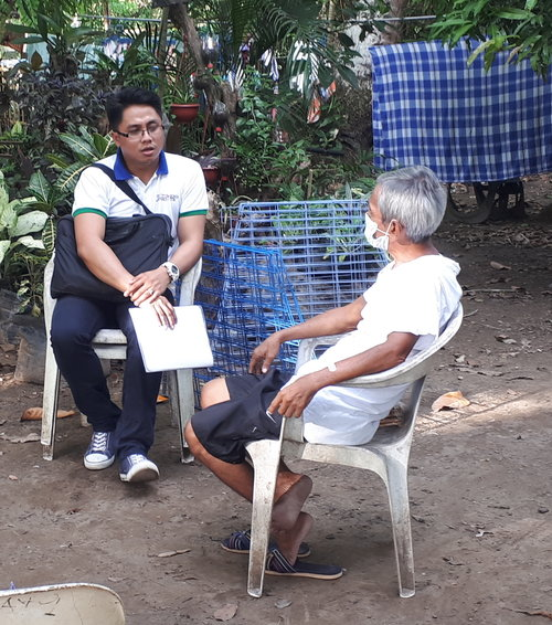 Mr. Adrian Hort Ramos, Region VI technical staff, talks to a TB patient during a home monitoring visit.